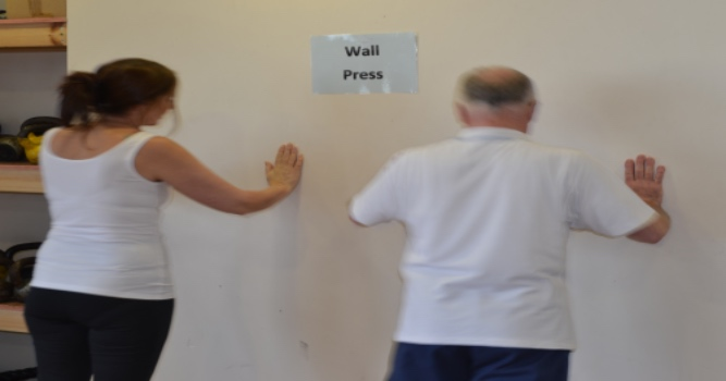patient doing a wall press up